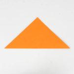 Origamipapier diagonal in der Hälfte gefaltet.