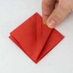 Falte die beiden unteren Seiten der Origamifigur zur mittleren Falz.