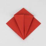 Origami Kranich falten. Falte die unteren Seite hin zur Mitte.