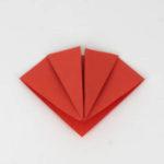 Knicke die obere Ecke des Origami Vogels nach hinten weg.