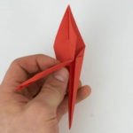 Die Spitze des Origami Kranischs wird umgeknickt.