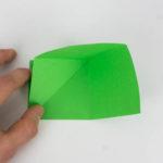 Origami Papagei - Die linke obere Ecke des Origamipapiers ist zur unteren linken Ecke gefaltet.