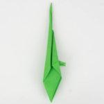 Den Origami Vogel wenden und die linke obere Seite zur Mitte falten.