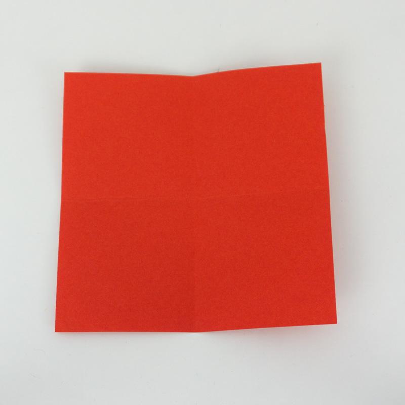 Das Origami Papier in der Hälfte falten.