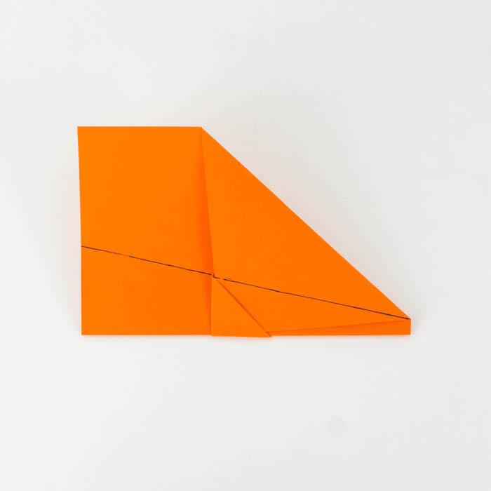 Die Tragflächen des Papierflugzeugs falten
