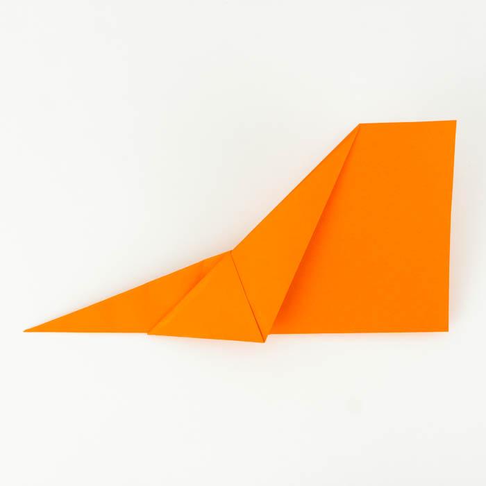 Der Papierflieger in der Hälfte, entlang der mittleren Falz gefaltet
