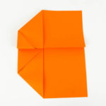 Die Tragflächen des Papierfliegers falten